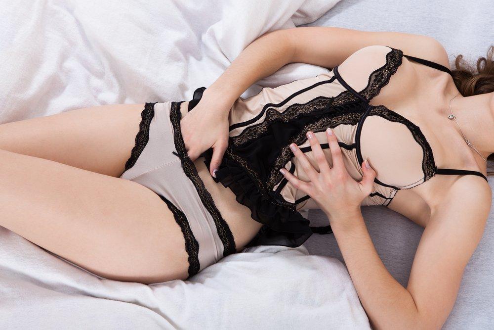 אשה על מיטה לבושה בבגד שחור
