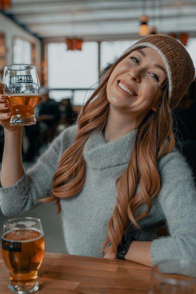 אשה עם כובע מחזיקה כוס בירה