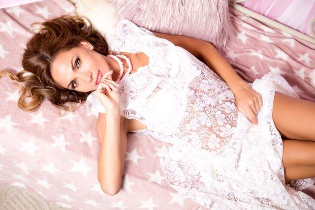 אשה לבושה בבגד לבן נשענת על מיטה