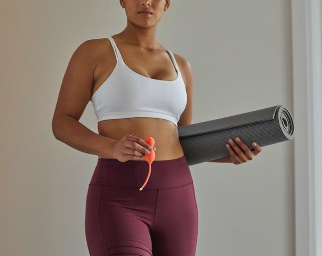 אשה באימון יוגה מחזיקה מזרון וביצי קגל